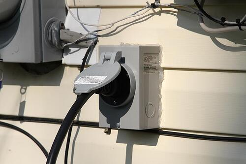 Power inlet box installed on the exterior of a home.