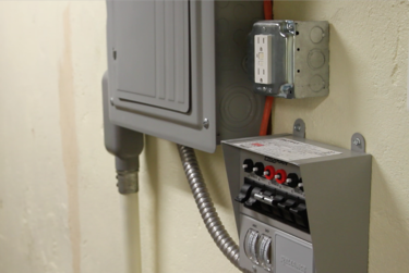 Manual transfer switch installed next to home electric panel