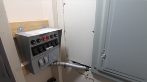 A manual transfer switch installed next to the home electric panel